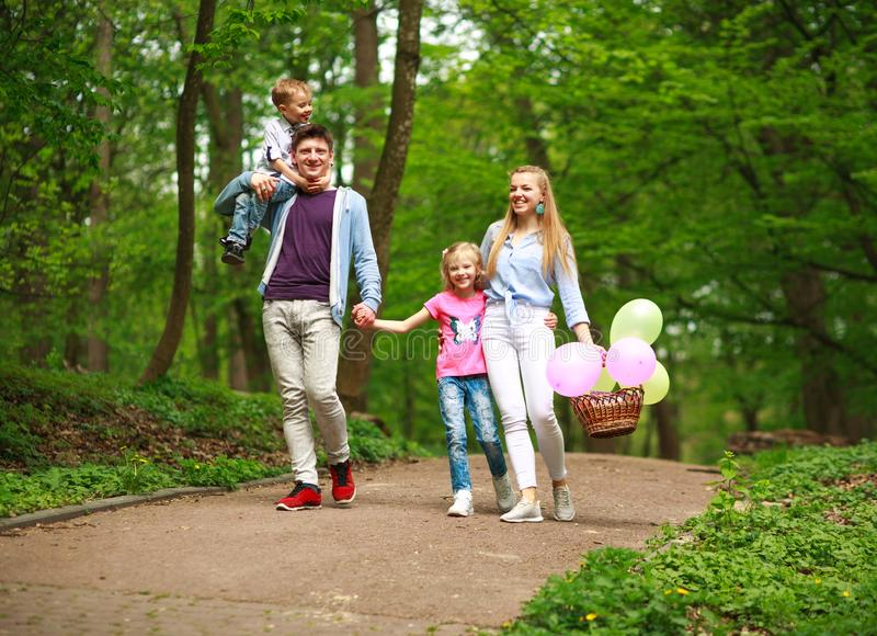 Happy young family with their two children are walking in summer forest park, parenthood vacations with kids royalty free stock photos