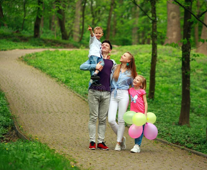Happy young family with their two children are walking in summer forest park, parenthood vacations with kids royalty free stock image