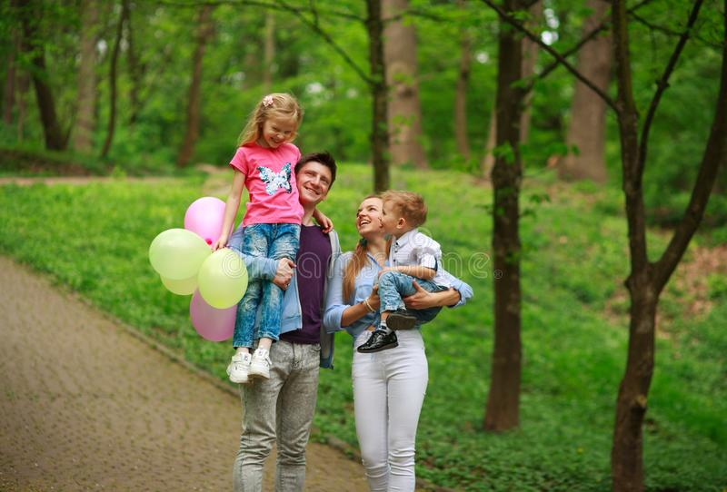 Happy young family with their two children are walking in summer forest park, parenthood vacations with kids royalty free stock photography