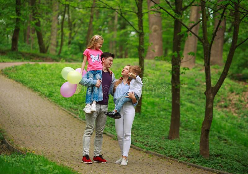 Happy young family with their two children are walking in summer forest park, parenthood vacations with kids stock photography
