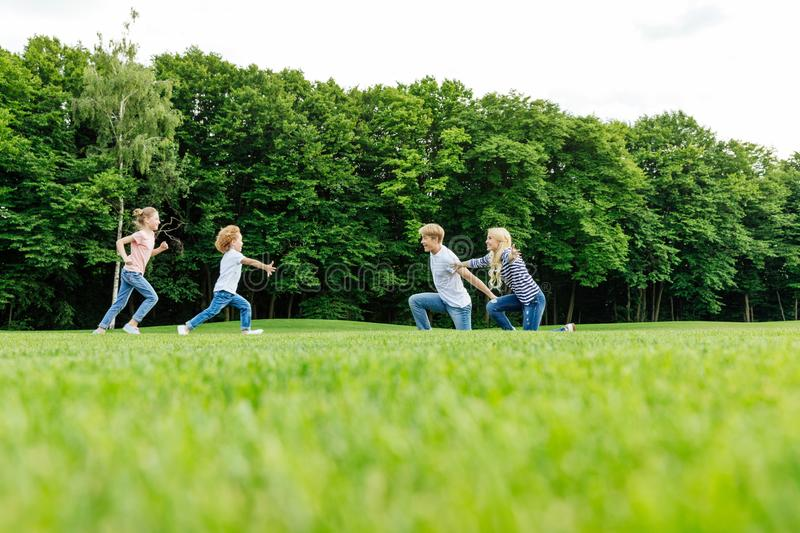 happy young family with two kids playing on green meadow stock image