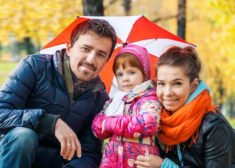 Happy young family under an umbrella stock image