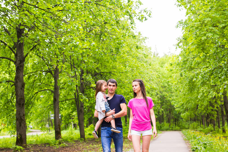 Happy young family walking in green nature. stock image