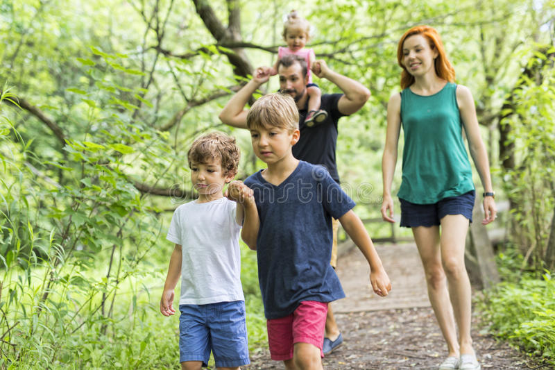 Happy young family walking outside in green nature royalty free stock images