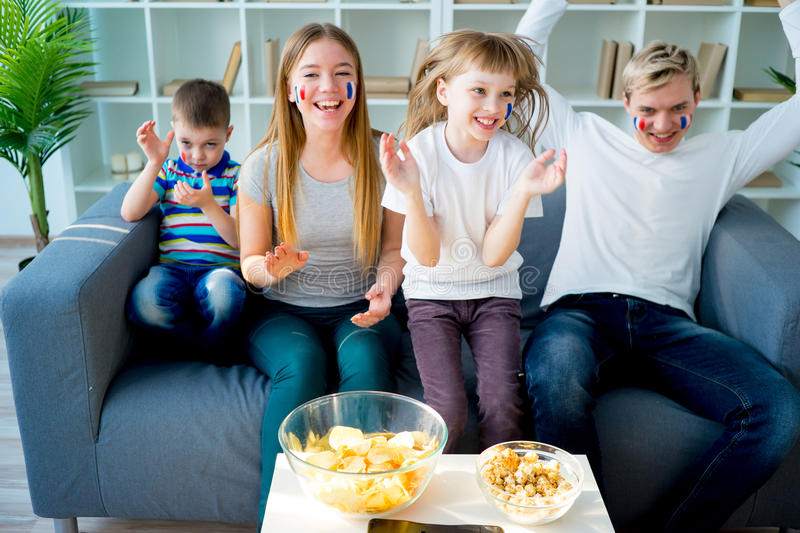 Happy young family watching television royalty free stock photography