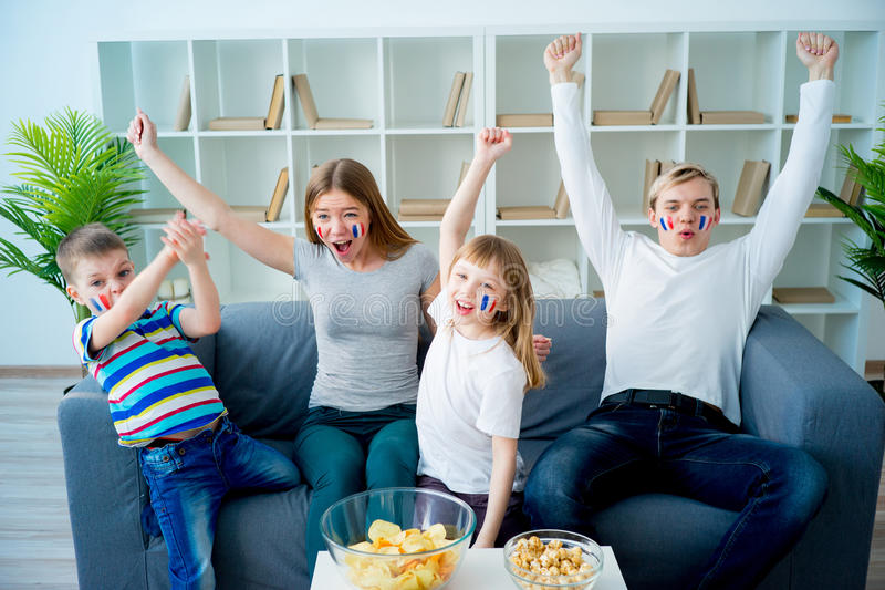 Happy young family watching television stock photography