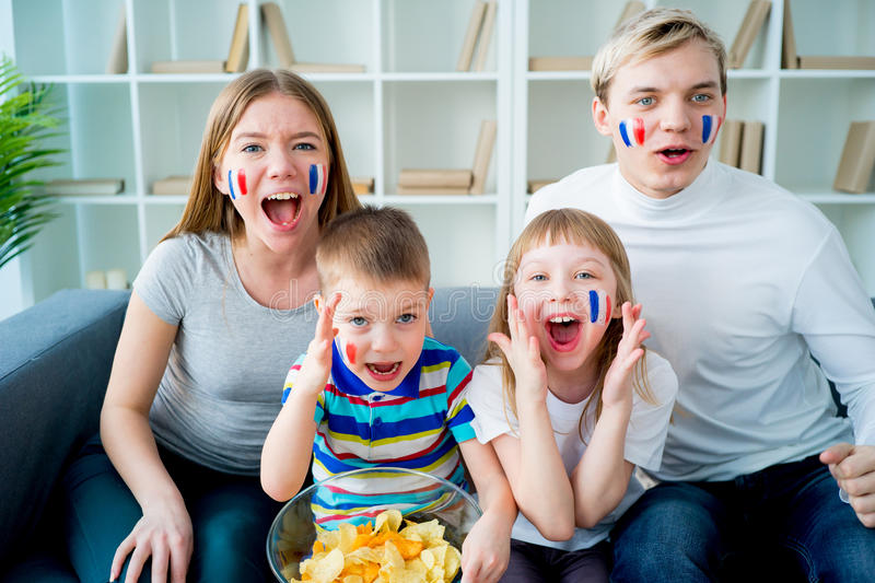 Happy young family watching television stock photos