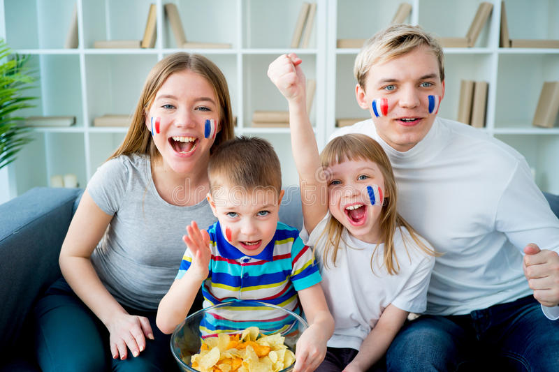 Happy young family watching television royalty free stock photo