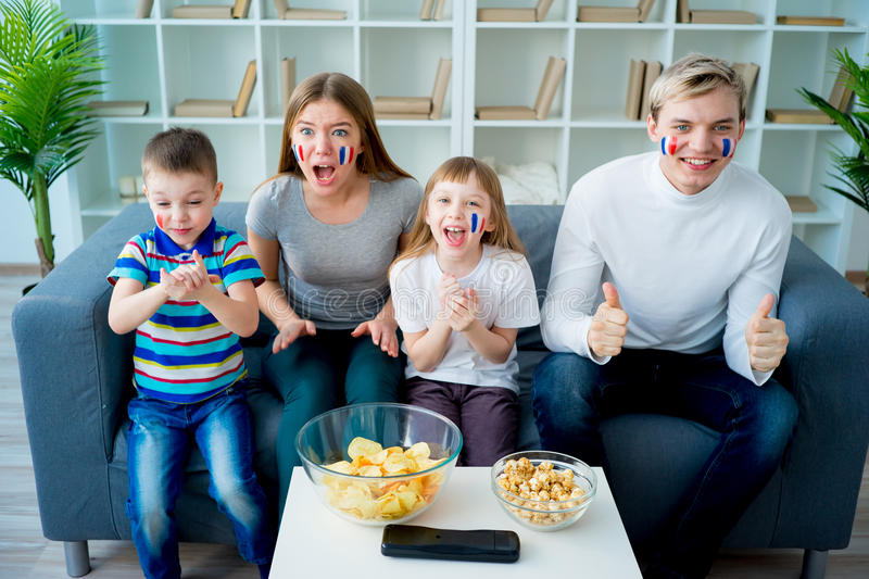 Happy young family watching television royalty free stock photos