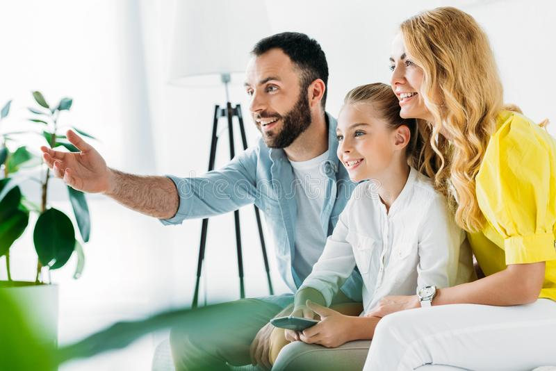 happy young family watching tv together at home and pointing royalty free stock photography