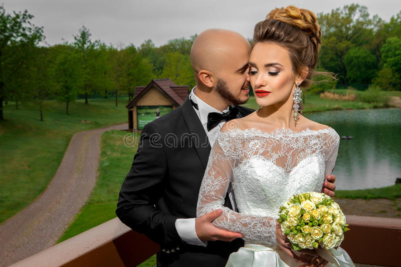 Happy young family in wedding suits hugging. Outdoors stock photo