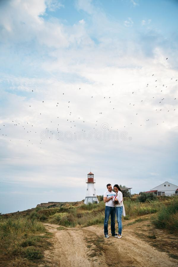 Happy young family in white t-shirts and blue jeans with a small daughter near to the white lighthouse, outdoors background with stock photos