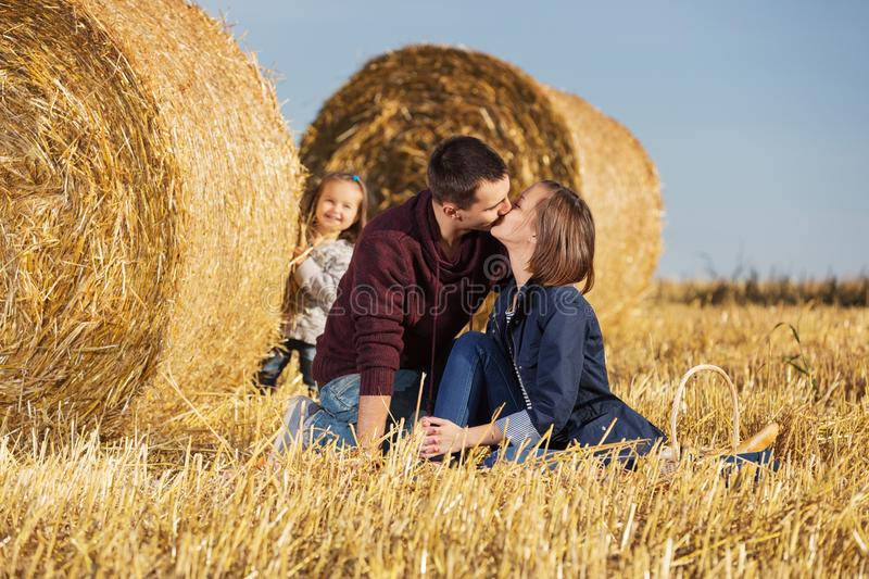 Happy young family with 2 year old girl next to hay bales. In harvested field stock images