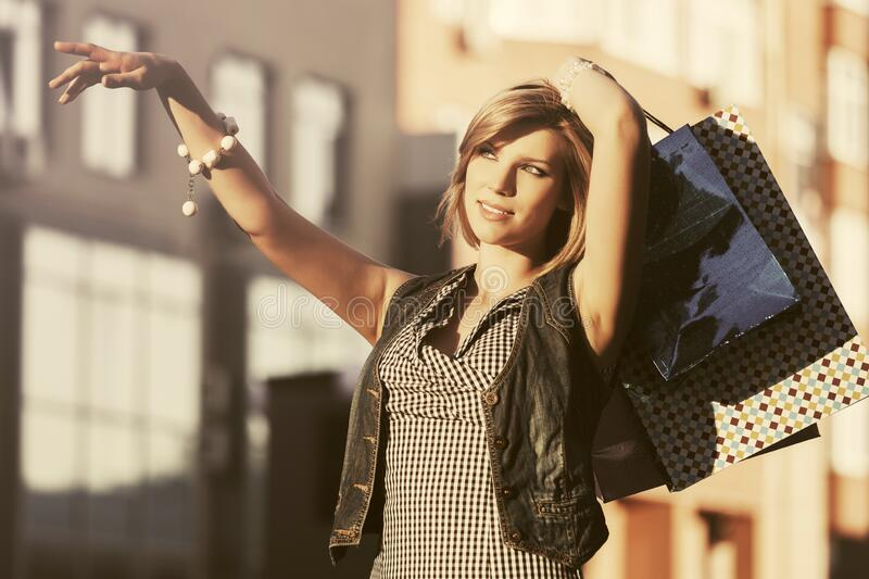 Happy young fashion woman with shopping bags walking on city street royalty free stock images