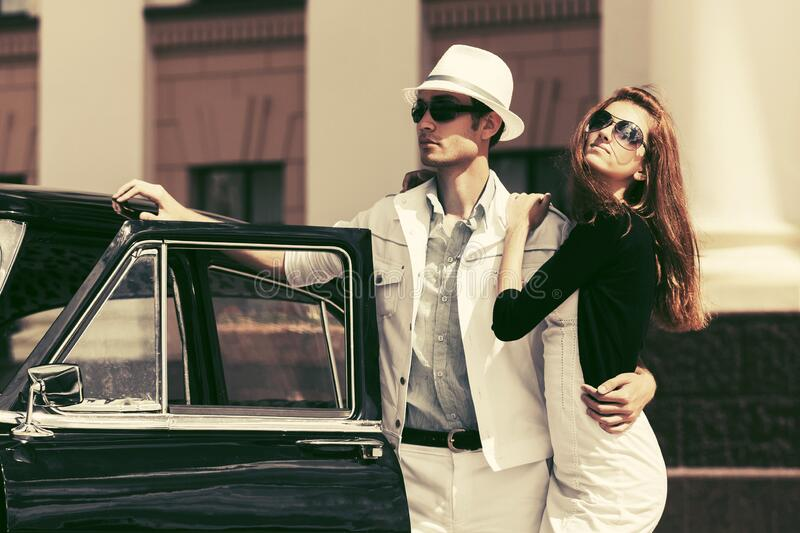 Happy young fashion couple next to vintage car stock photo
