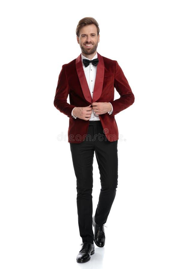 Happy young fashion model fixing red velvet coat stock photo