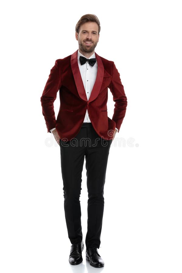 Happy young fashion model smiling and wearing red velvet tuxedo stock images