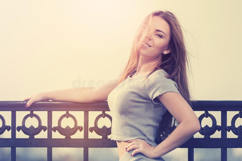 Happy young fashion woman in grey crop top and skirt suit leaning on railing stock photo