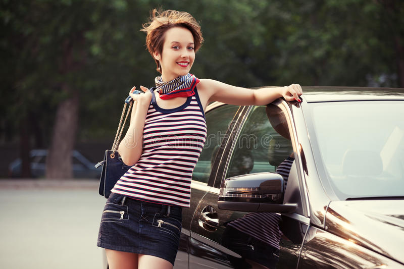 Happy young fashion woman with handbag next to her car. Outdoor stock images