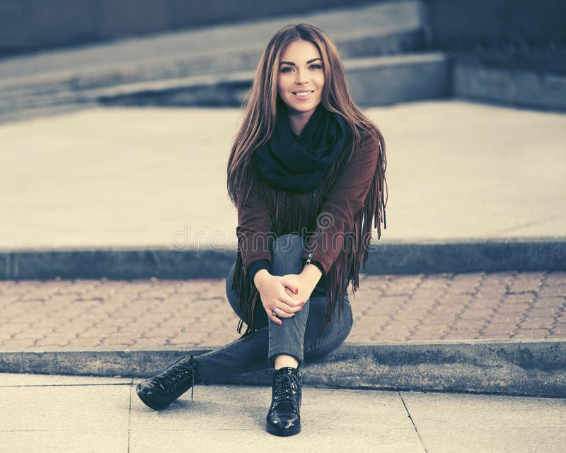 Happy young fashion woman in leather jacket sitting on sidewalk on city street. Happy young woman sitting on city street Stylish fashion model in leather fringe stock images