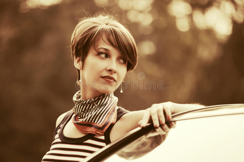 Happy young fashion woman in tank top next to her car. Happy young fashion woman with pixie haircut in tank top next to her car outdoor royalty free stock photos