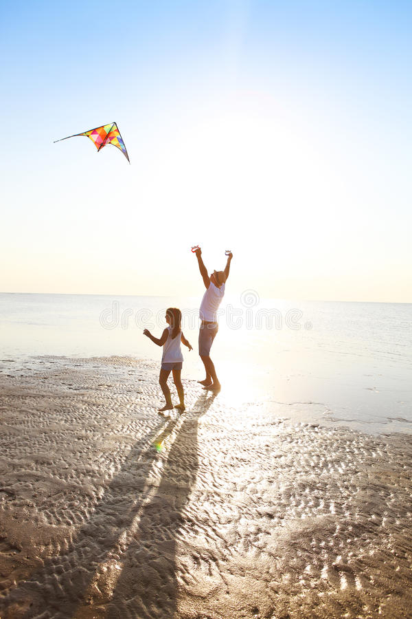 Happy young father with daughter with flying a kite on the beach stock photo