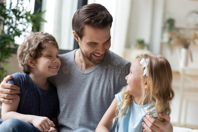 Happy young father embracing two little laughing kids. stock image
