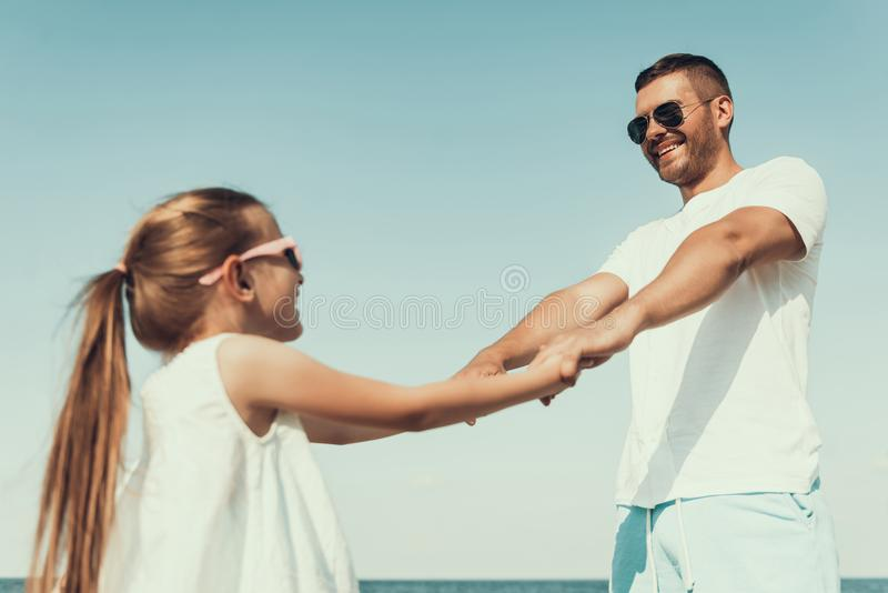 Happy young father in sunglasses turns with daughter, holding hands. royalty free stock images