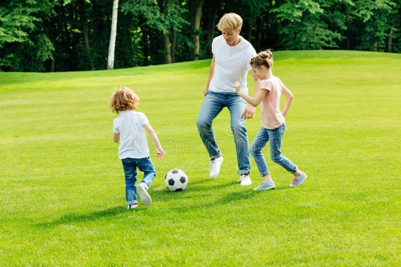 Happy young father with two adorable children. Playing soccer on green lawn at park royalty free stock image