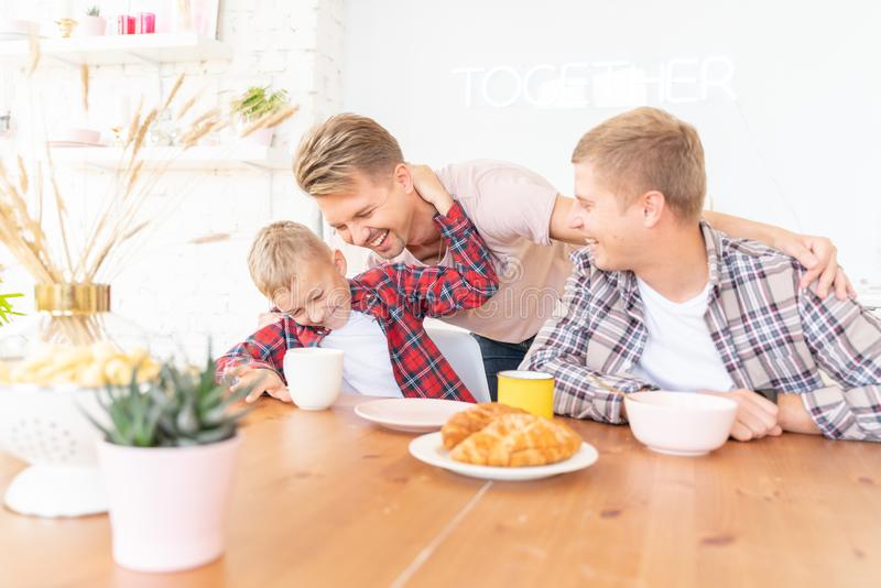 Happy young fathers and son have breakfast in the kitchen, gay family with a child, time together, parenting in homosexual royalty free stock photography