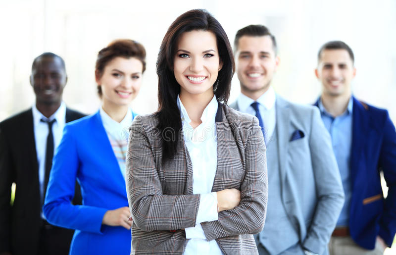 Happy young female business leader standing in front of her team stock photo