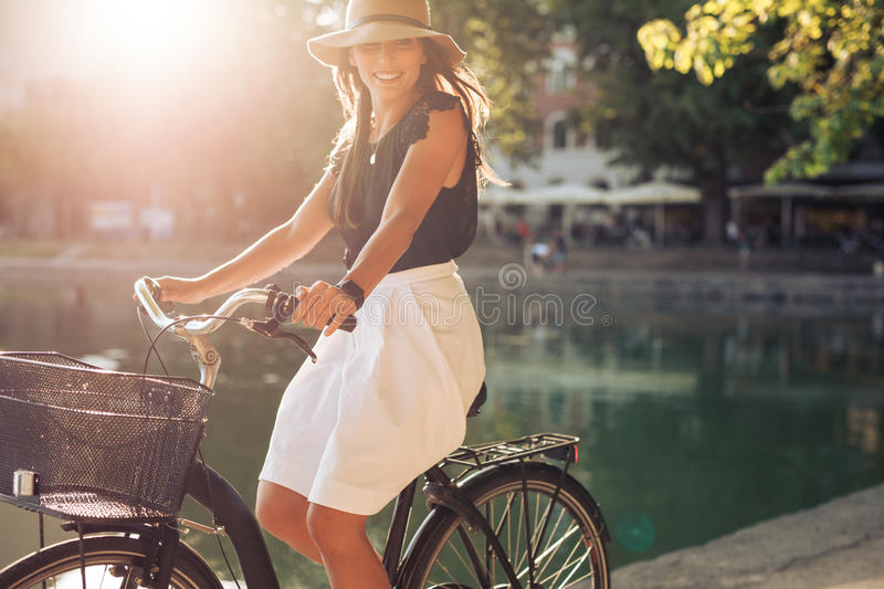 Happy young female cycling by a pond royalty free stock images