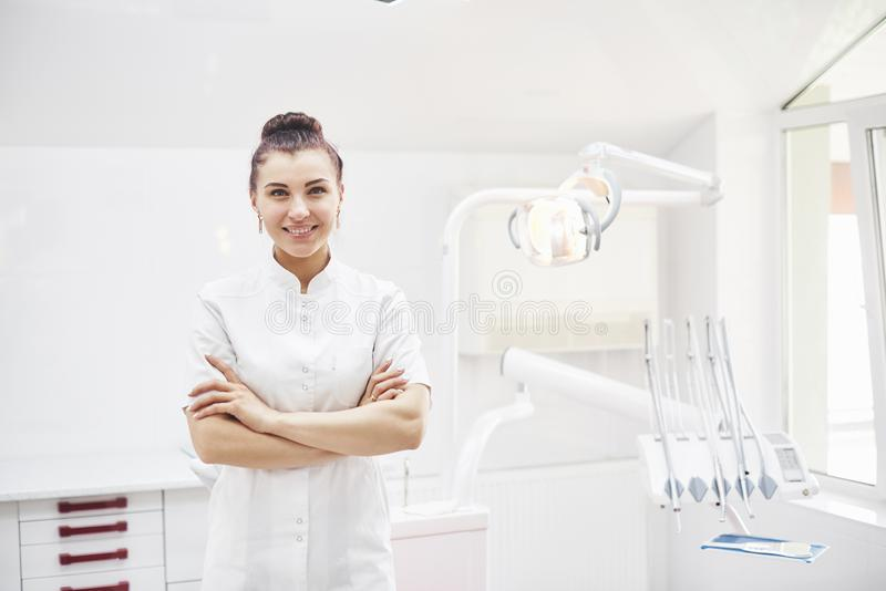 Happy young female dentist with tools over medical office background. Stomatology and healthcare concept royalty free stock photo