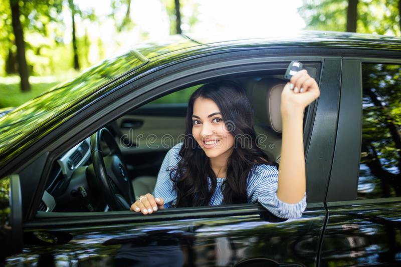 Happy female driver showing car key in her new car royalty free stock image