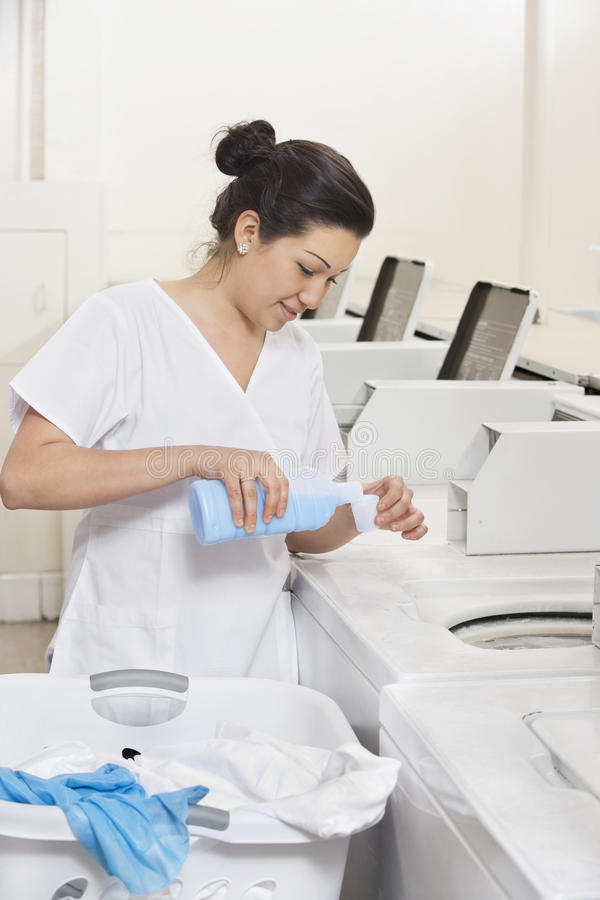 Happy young female employee pouring detergent in washing machine Laundromat stock photos