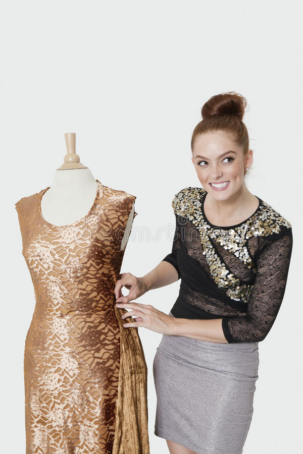Happy young female fashion designer working on an outfit over gray background stock photo