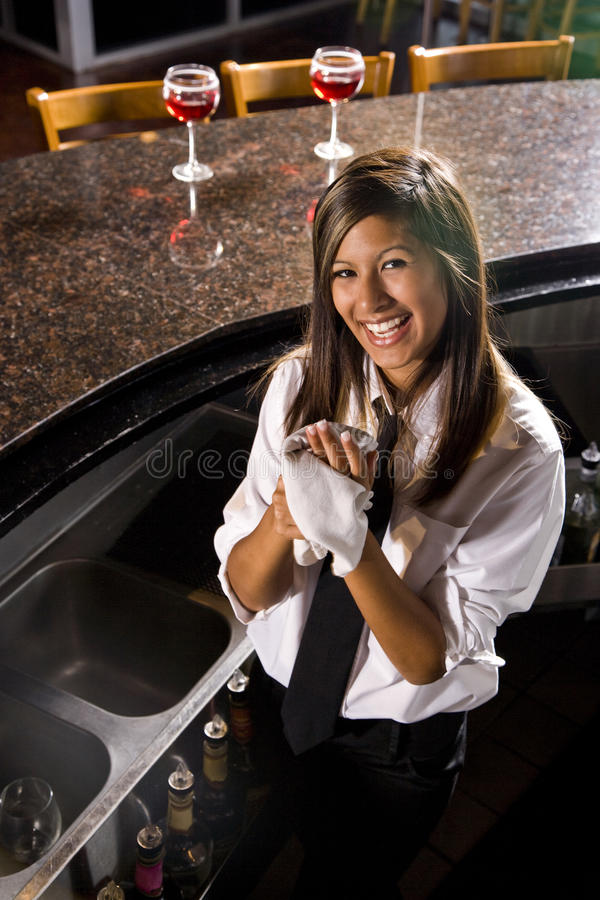 Happy young female Hispanic bartender. Attractive Hispanic female bartender standing behind counter drying her hands stock photo