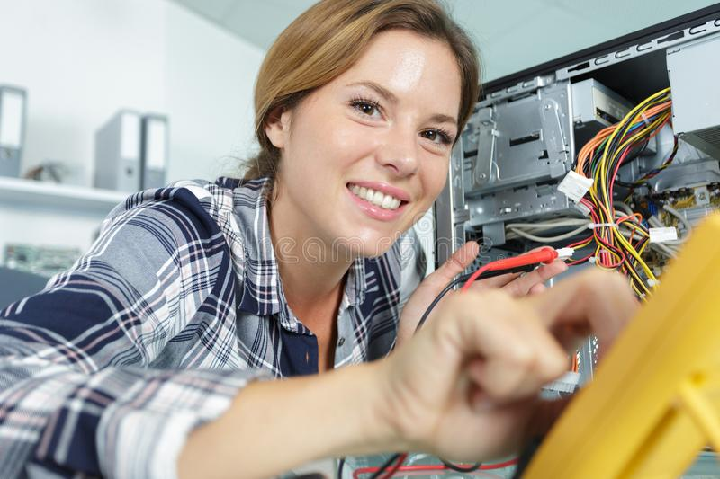 Happy young female pc technician in class royalty free stock photo
