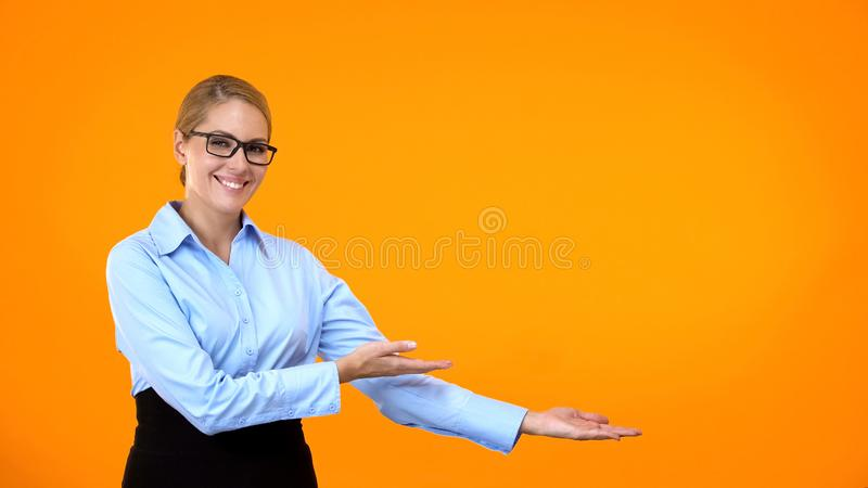 Happy young female pointing hands on bright background, template presentation stock image