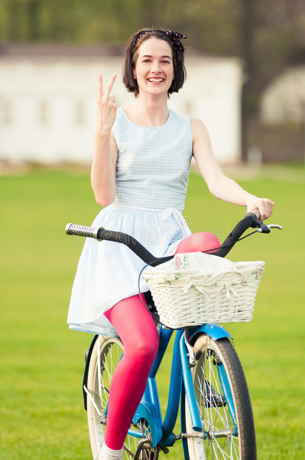 Happy young female standing on bicycle and showing victory gestu. Happy young female standing on bicycle and showing victory or peace gesture acting cheerful stock image