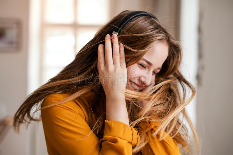 A young female student with headphones having fun. A happy young female student with headphones having fun royalty free stock image