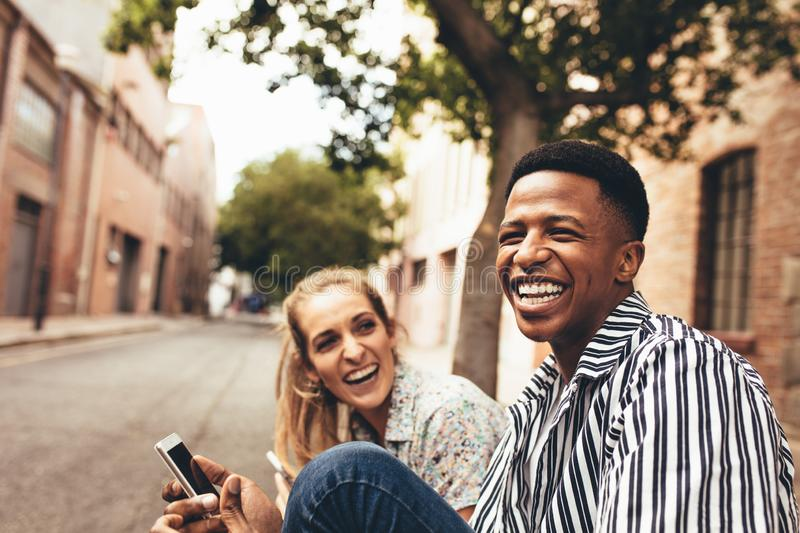 Happy young friends. Cheerful multiracial male and female friends sitting outdoors with mobile phone. Happy young friends outdoors stock image