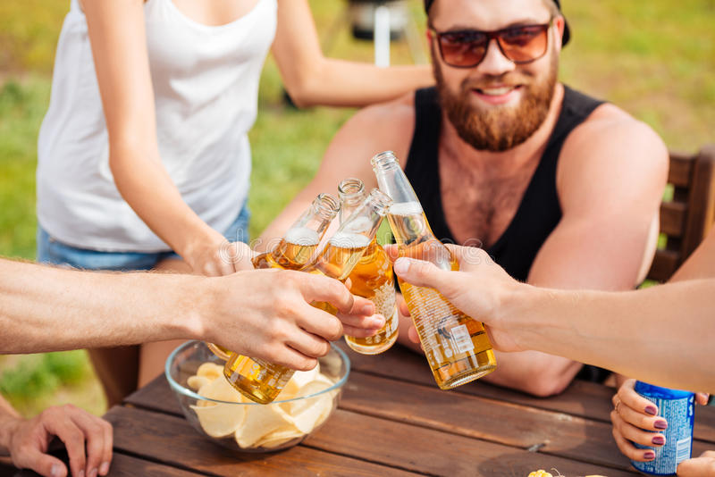 Happy young friends drinking beer and cekebrating together stock image