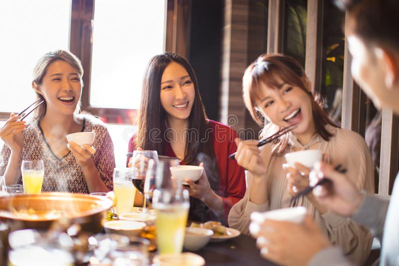 Young friends eating hot pot in restaurant royalty free stock photography