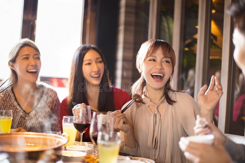 Young friends enjoy dinner in hot pot restaurant royalty free stock image