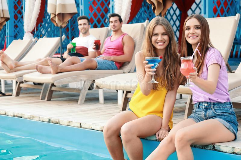 Happy young friends with fresh summer cocktails relaxing near stock images