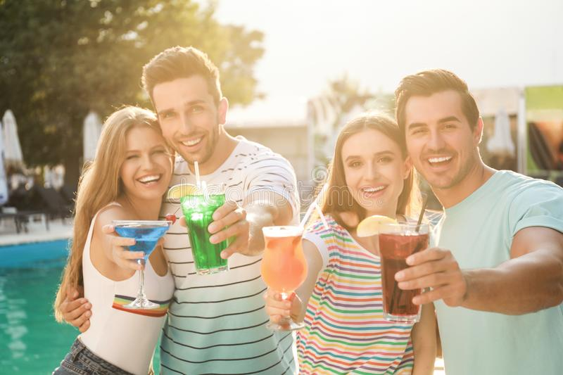 Happy young friends  fresh summer cocktails relaxing near swimming pool stock photography
