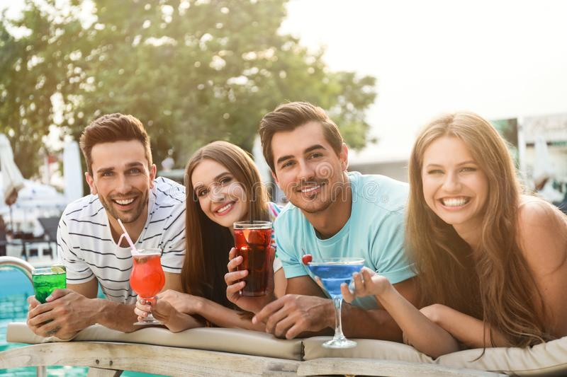 Happy young friends with fresh summer cocktails near swimming pool stock image