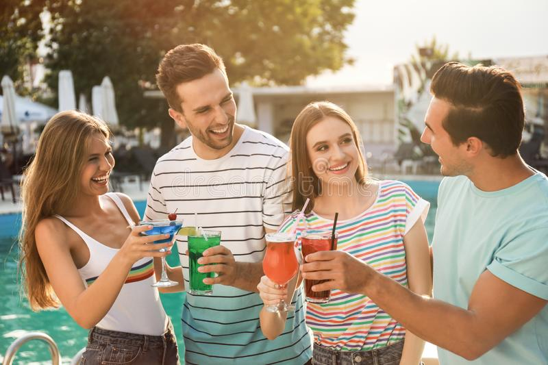 Happy young friends with fresh summer cocktails near swimming pool stock photo