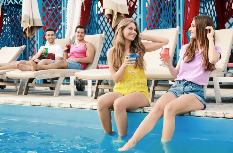 Happy young friends with fresh summer cocktails near swimming pool royalty free stock image